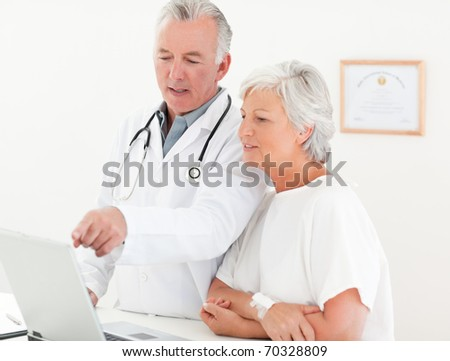 Doctor and his patient looking at the laptop