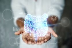 Doctor and holographic bowel scan projection with vital signs and medical records. Concept of new technologies, body scan, digital x-ray, abdominal organs, modern medicine