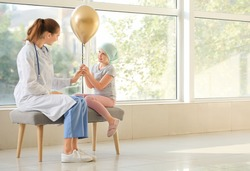 Doctor and little girl with golden balloon in clinic. Childhood cancer awareness concept