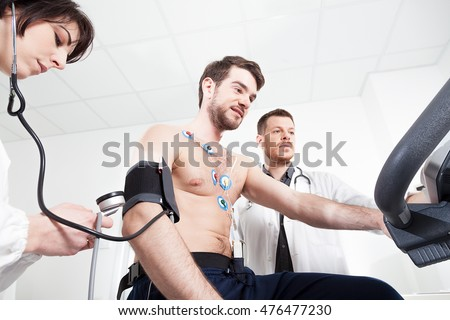 Doctor and nurse assist the patient during the medical examination of cardiac stress test