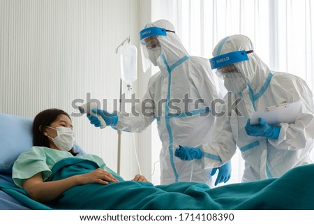 doctor and nurse in personal pretective equipment or ppe treating the asian woman patient with covid-19 or coronavirus infection in the isolation unit in the hospital during pandemic. medical concept