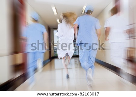 Doctor and nurse running in passageway of hospital