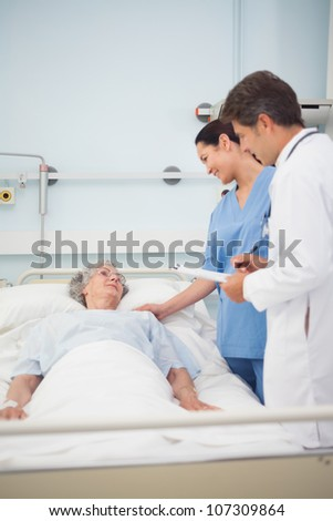 Doctor and nurse speaking to a patient in hospital ward