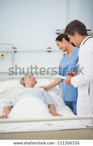 Doctor and nurse talking with a patient in hospital ward