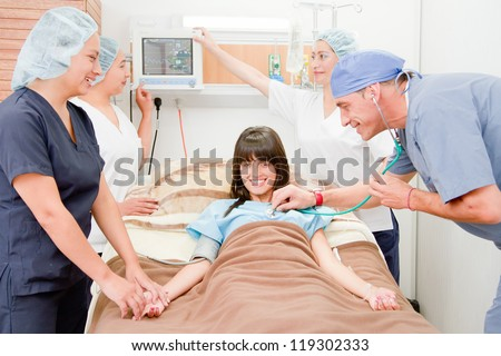 Doctor  and nurses checking heart beat of patient in bed with stethoscope with nurse adjusting I.V