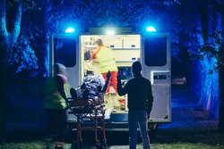 Doctor and paramedic of emergency medical service take care of old ill man. Team of emergency medical service rescuing old patient. Concepts health care, rescue and goodbye.
