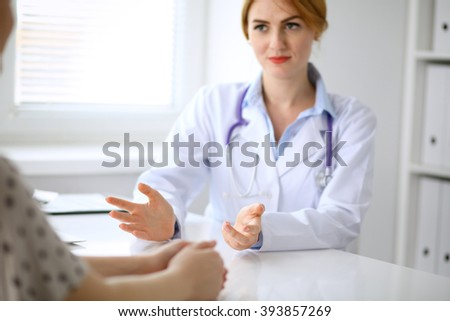 Doctor and patient are discussing something, just hands at the table #393857269