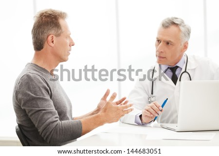Doctor and patient. Doctor listening to the patient while he is telling about his problems