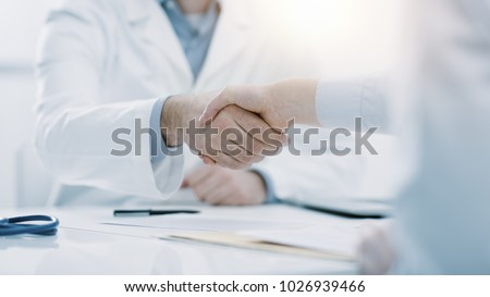 Doctor and patient shaking hands in the office, they are sitting at desk, hands close up