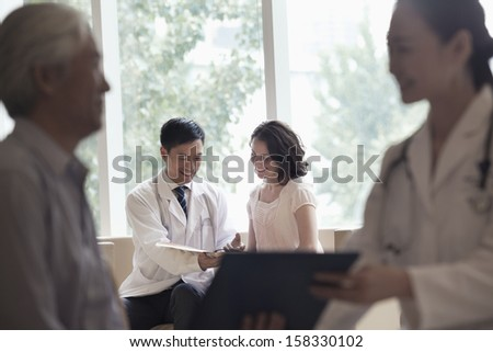 Doctor and patient sitting down and discussing medical record in hospital