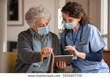 Doctor and senior woman going through medical record on digital tablet during home visit wearing face mask. Old woman with nurse with surgical mask and using digital tablet during coronavirus pandemic Foto stock ©