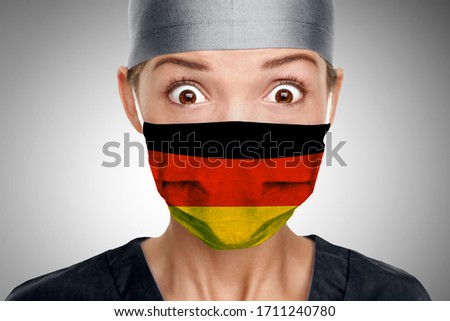 Doctor Asian woman shocked German doctor for COVID-19 crisis help with Germany flag on surgical mask. Healthcare workers needing PPE help to fight COVID-19 Coronavirus . Photo stock ©