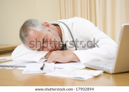 Doctor asleep on desk
