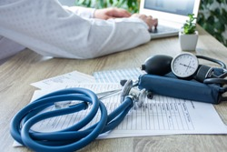 Doctor at work on the computer in the blurry background, in the foreground - a stethoscope with sphygmomanometer on medical documents on the table. Scene of doctor working in a modern medical office