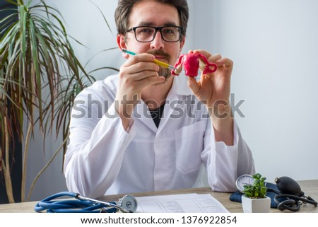 Doctor at workplace in office during appointment looks into camera shows patient anatomic model of uterus with focus on hand on ovaries . Professional medical diagnosis diseases of reproductive system