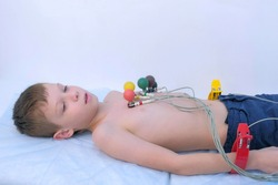 Doctor cardiologist preparing child boy to cardiogram heart procedure, side view. Woman cardiologist making heart cardiogram for child boy lying on couch putting sensors on chest, hands closeup.