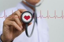 Doctor (cardiologist) with stethoscope in hand and EKG (electrocardiogram) graph monitor, health and medical concept.