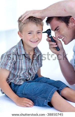 Doctor checking a child patient' s ears