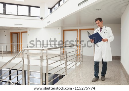 Doctor checking folder in hospital corridor