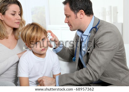 Doctor checking little boy's ear infection