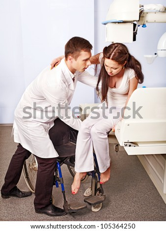 Doctor checking patient  in x-ray room.