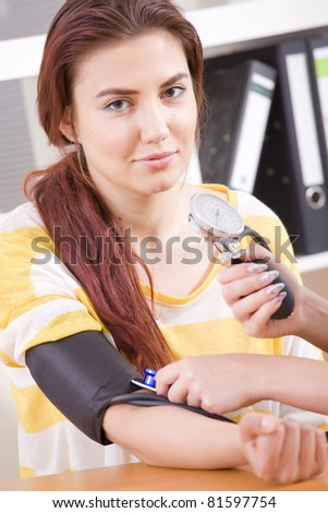 doctor checking the blood pressure of a female patient