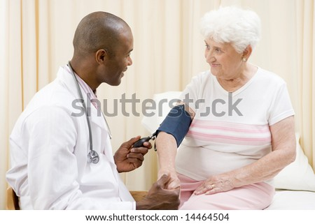 Doctor checking woman's blood pressure in exam room smiling