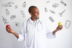 Doctor comparing apples with hand drawn medical sketches. Healthy nutrition concept. Isolated front closeup view with medicine icons on background.