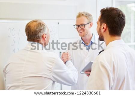 Doctor congratulating colleague for successful teamwork #1224330601