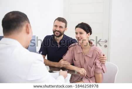 Doctor consulting young couple patients in fertility clinic about IVF or IUI. Family and infertility consultation concept Foto stock ©