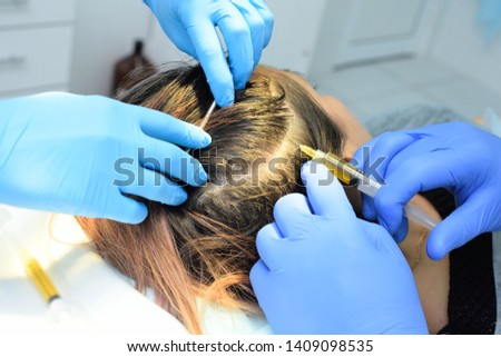 doctor cosmetologist dermatologist injects the plasma into the scalp of the patient. Plasma treatment, plasmolifting or PRP method point the introduction of the patient's own plasma enriched with plat #1409098535