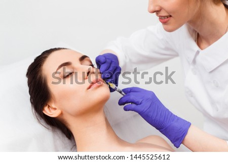 Doctor cosmetologist injects patient's face #1445525612