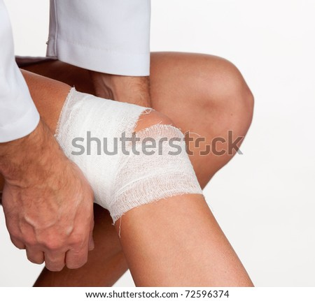 Doctor cover the knee of patient by bandage isolated on a white background