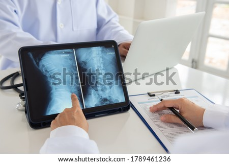 doctor diagnose spine lumber vertebrae x-ray image on digital tablet for diagnose Herniated disc disease with radiologic technologist team. Foto d'archivio ©