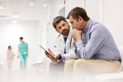 Doctor discussing over digital tablet with mature patient at hospital