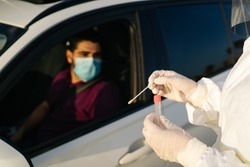 Doctor doing a PCR test COVID-19 on a patient through the car window. PCR diagnostic for Coronavirus presence,doctor in PPE holding test kit