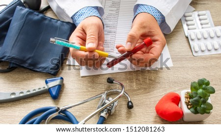 Doctor during consultation held in his hand and shows patient laboratory tube with blood. Counseling of transfusion, blood and hematologic diseases and pathology like anemias, cell cancer, hemophilia