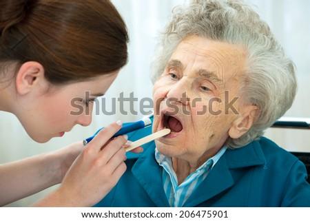 Doctor examines elderly woman for sore throat