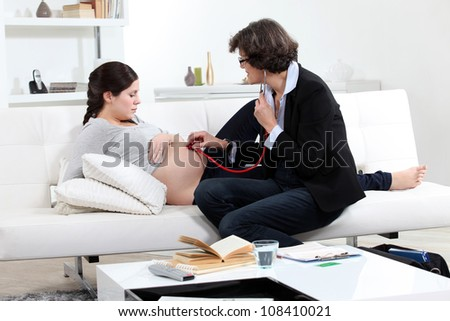 Doctor examining a pregnant woman at home