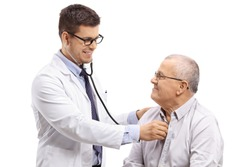 Doctor examining an elderly patient with a stethoscope isolated on white background