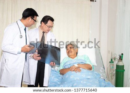 Doctor examining chest x-ray film  which doctor holding x-ray, x-ray film of older woman patient at hospital #1377715640