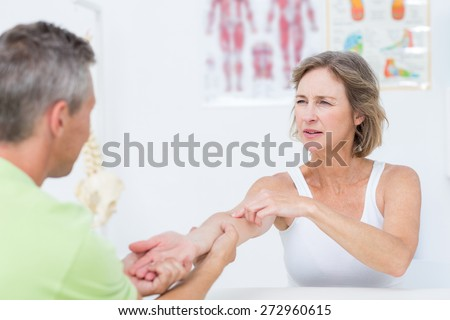 Doctor examining his patients arm in medical office