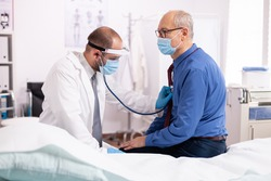 Doctor examining patient lungs using stethoscope wearing face mask as safety precaution in time of covid19. Medical practitioner wearing face mask consulting senior man in examination room during