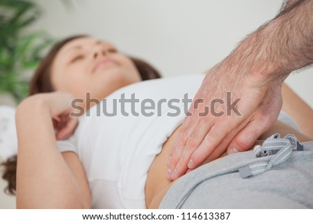 Doctor examining the stomach of his patient in a room