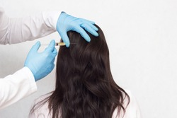 Doctor gives a patient a plasmaplifting shot to the patient s head to improve the growth and quality of the hair, plasma therapy