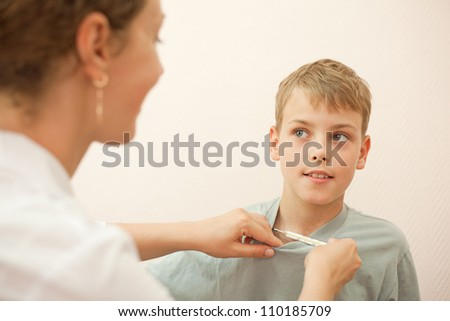 Doctor gives thermometer little boy and hold his t-shirt, focus on boy