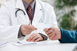 doctor giving a prescription to his patient