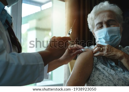 Doctor giving injection coronavirus vaccine to the elderly patient, elderly wearing medical mask, general practitioner visiting her at home, elderly health care concept, selective focus