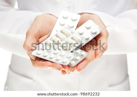 Doctor giving many pills; closeup of doctor's hands holding many medicines