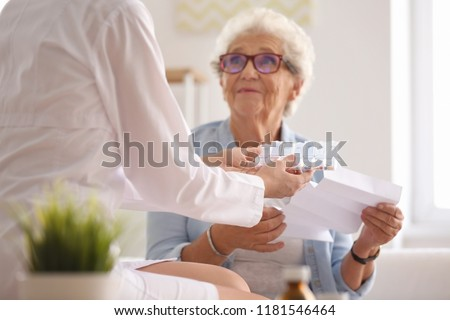 Doctor giving medicine and instruction to senior woman at home